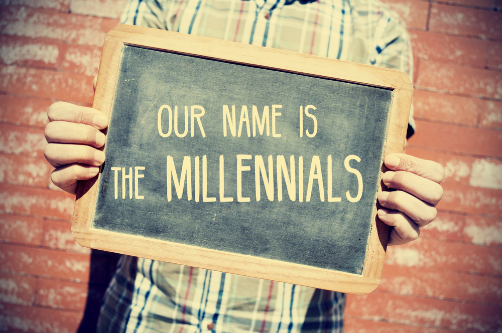 closeup of a young man holding a chalkboard with text our name is the millennials in front of a brick wall, slight vignette added